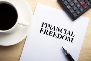 Text Financial Freedom is on the white paper with coffee, calculator and ball pen aside.